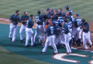 MOSH PIT: Miami celebrates after a home run Saturday night. Miami went on to win, 14-10, forcing a deciding third game. Photo Credit: Christina De Nicola // Hurricane Staff