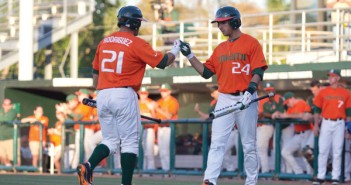 Freshman Julian Santos fist bumps his teammate, Rony Rodriguez, senior, as he comes up to bat in Saturday's game against Maryland. Miami won 9-1, for the thrid straight ACC victory. Zach Beeker // Staff Photographer