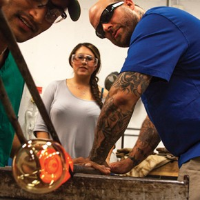 Alex Adams, glassblowing artist and professor, helps Nirmal Pathak create a glass at the Glassblower's Guild while senior Lara Lackstein looks on. Hadley Jordan // Contributing Photographer