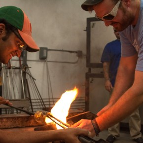 Seth Fairweather, Resident Artist, helps Nirmal Pathak create a glass during the Glassblower's Guild on Tuesday night. Hadley Jordan // Contributing Photographer