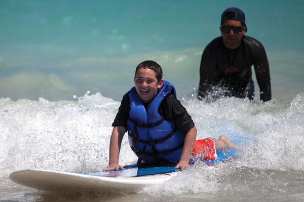 Jack Ruderman, 9, smiles as he learns how to surf. One of the camp lifeguards, Radael Ruiz, 36, helps him get the board in the correct position for the wave. Cayla Nimmo // Photo Editor