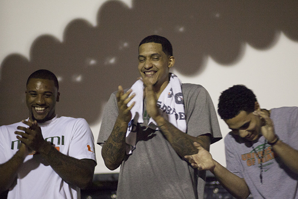 "Junior Erik Swoope, senior Julian Gamble and sophomore Shane Larkin of the Men's Basketball team laugh onstage during a thank you ceremony hosted by Category 5. Coach Larranaga and the team were presented with a plaque and a basketball signed with messages from the students. Larranaga thanked the students for their high attendence this season by suggesting that they were the ""6th man on the team."" Monica Herndon // Assistant Photo Editor"