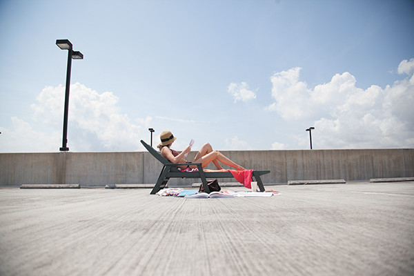 Junior Kate Maier sunbathes on roof of the UV Albenga garage on Monday afternoon. Photo Illustration. Monica Herndon // Assistant Photo Editor