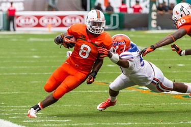 Sophomore Duke Johnson (8) powers past a Gators defender. The Hurricanes defeated the Gators 21-16. Nick Gangemi // Assistant Photo Editor