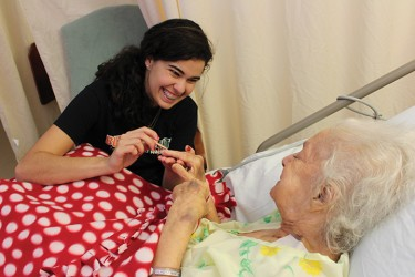 During the UGenerations visit to the Floridean Nursing Home on Saturday morning, Junior and Vice President of UGenerations, Gaby Lins gives resident Gladys Martinez a manicure. Hallee Meltzer// Staff Photographer