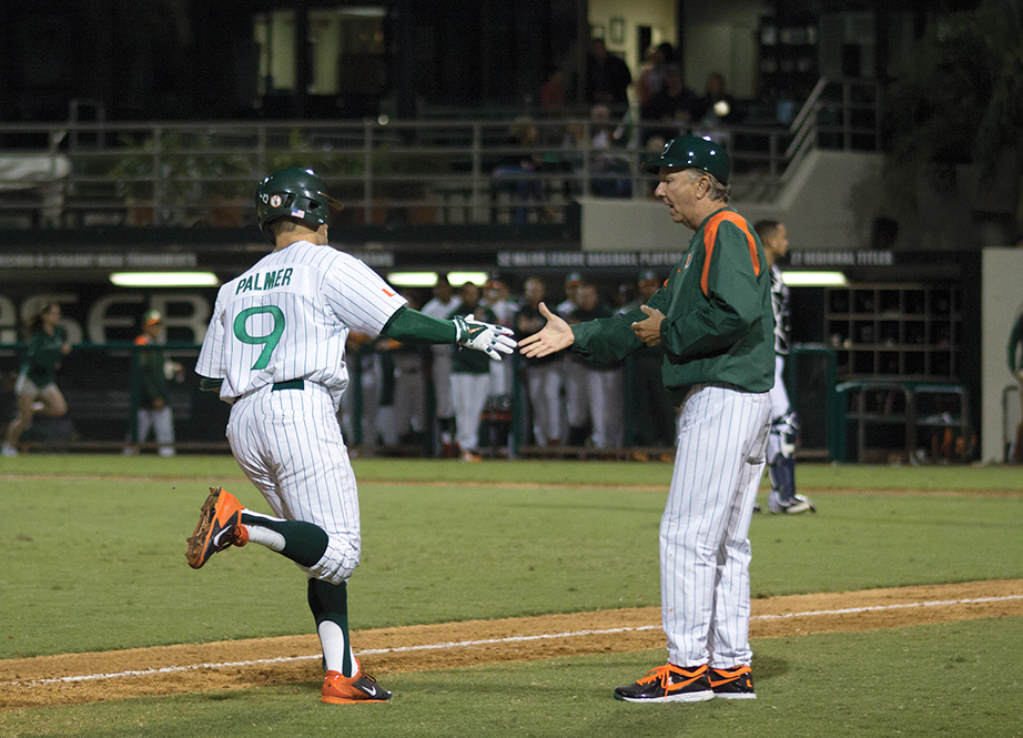 Senior Tyler Palmer celebrates with baseball head coach Jim Morris after hitting a homerun during the first game of the season on Friday night. The Canes won the series against Maine. Monica Herndon // Photo Editor