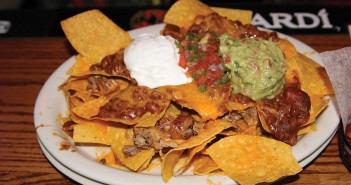 The Humongous BBQ Nachos at Brother Jimmy's meld Mexican with barbecue. The tortilla chips are topped with the traditional chili, cheese, salsa, guacamole and sour cream, but they also come with BBQ beans and the choice of pulled pork or chicken. Lyssa Goldberg // Contributing Photographer