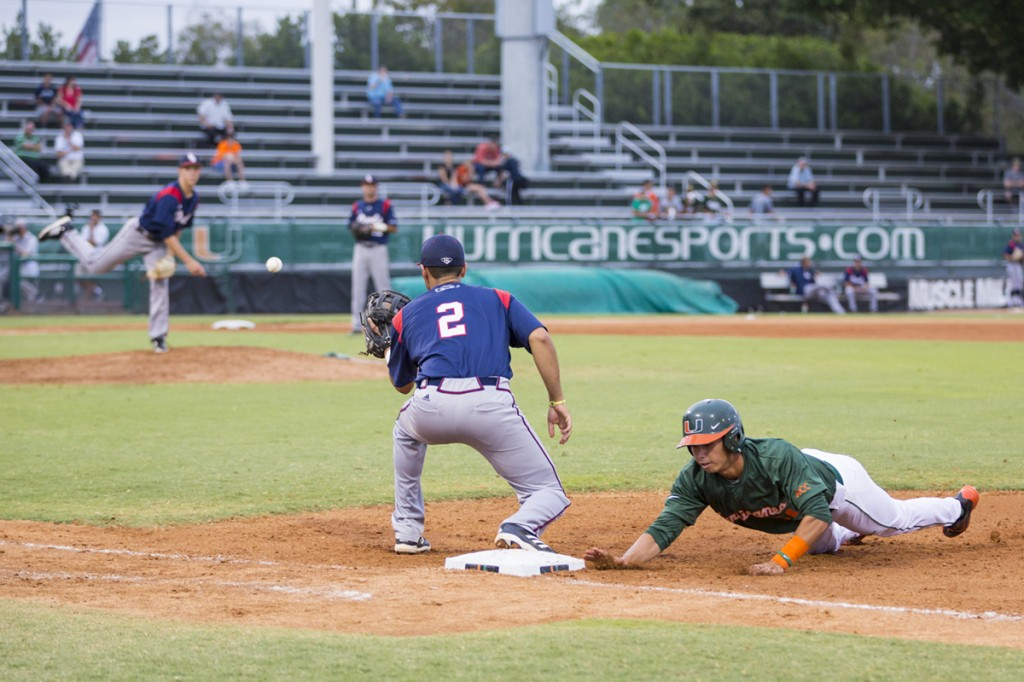 Sophomore Brandon Lopez slides to first as the FAU pitcher makes a pickoff attempt during Wednesday evening's game.  Nick Gangemi // Assistant Photo Editor
