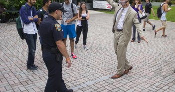 "Wearing googles that simulate alcohol impairment, Dean of Students Ricardo Hall attempts to complete a sobriety test. The annual safety fair took place on Thursday at the Rock. This year, the Florida Department of Transportation District Six partnered with UM to promote a ""Put It Down"" campaign. The fair featured booths offering information about texting and driving, and a a car roll simulator showed students the impact of rollover accidents. Mothers Against Drunk Driving handed out brochures and Ms. University of Miami promoted her campaign against texting and driving. Victoria McKaba // Staff Photographer"