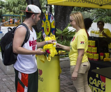 Junior Jesse Schilling grabs free coffee and a shirt from Cafe Bustelo on the Rock Tuesday. Cafe Bustelo promoted its scholarship program, which recently became eligible to Hispanic students. Giancarlo Falconi // Staff Photographer
