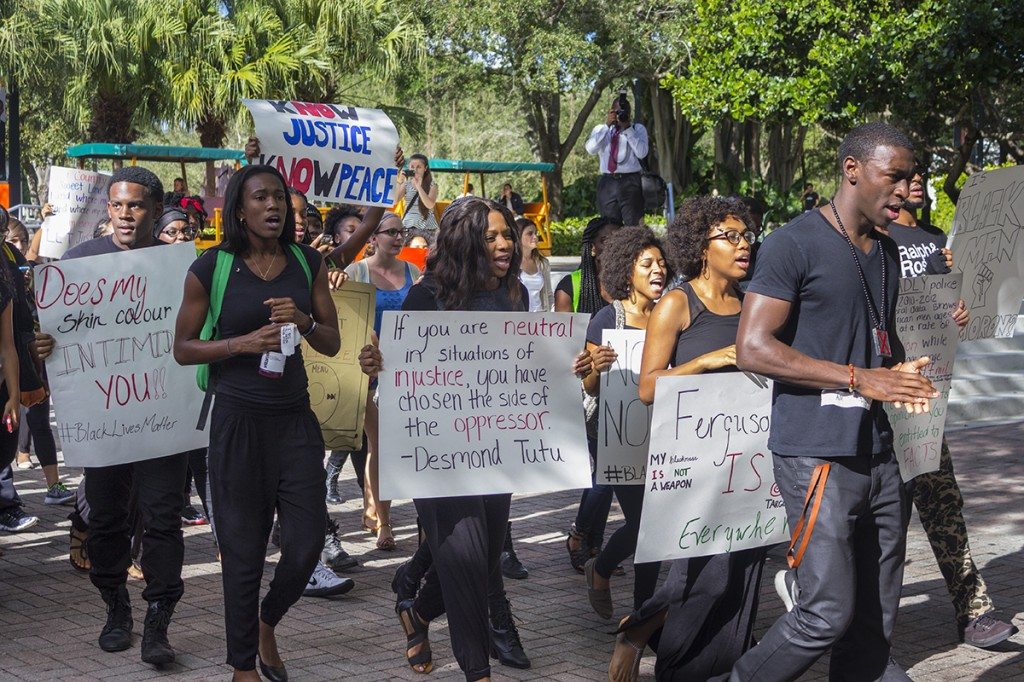 "Various student groups organized a ""#BlackLivesMatter"" demonstration that took place on campus Wednesday afternoon. Protestors marched around campus, staged a ""die in"" on the rock, and hosted a guest speaker. Giancarlo Falconi // Staff Photographer"