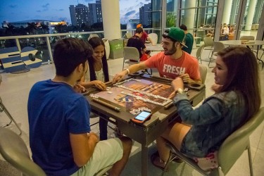 Junior Christian Perez, freshman Patricia Colon, junior Daniel Cantrelle and freshman Ashley Bahamonde (left to right) play a game of dominos on the Moss Terrace as part of  Week of Cuban Culture.
