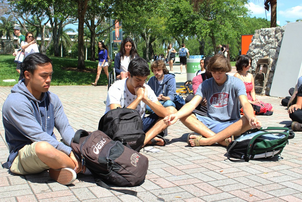 Students sit for peace at the UC Rock Monday afternoon. Giancarlo Falconi // Staff Photographer