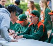 Baseball head coach Jim Morris signs posters and other memorabilia for fans during February's Fan Fest held at Alex Rodriguez Park at Mark Light Field to open the 2015 season. File Photo by Nick Gangemi