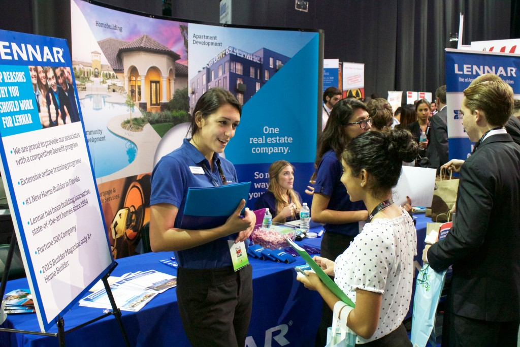 Freshman Diaya Tulshi speaks to a representative from Lennar, a home development company which focuses on multigenerational living, at the Career Expo Friday afternoon. Kawan Amelung // Contributing Photographer