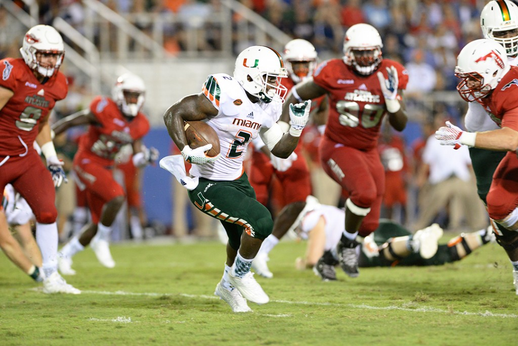 Sophomore running back Joseph Yearby (2) runs the ball through FAU defenders during Friday's game at Howard Schnellenberger Field at FAU Stadium. The Canes won 44-20, extending their winning record to 2-0 record. Courtesy Jessica Marshall // Caneshooter.com