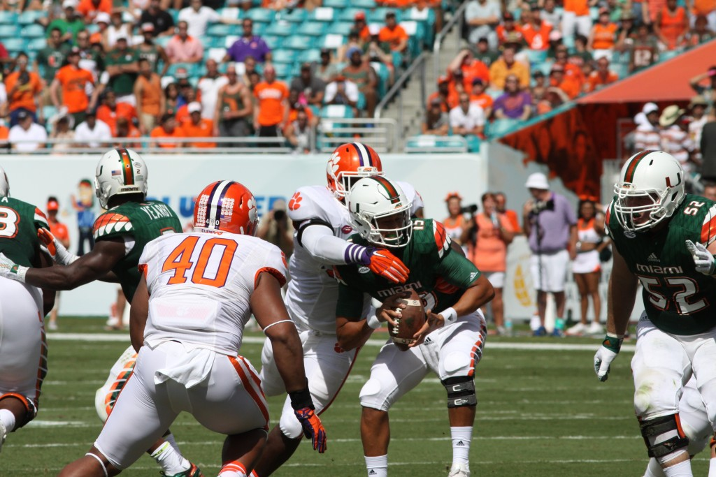 Sophomore quarterback Brad Kaaya (15) takes a hit from Clemson defenders in the first quarter of last week's game against Clemson. Kaaya later left the game after getting sacked early in the second quarter. Hallee Meltzer // Photo Editor