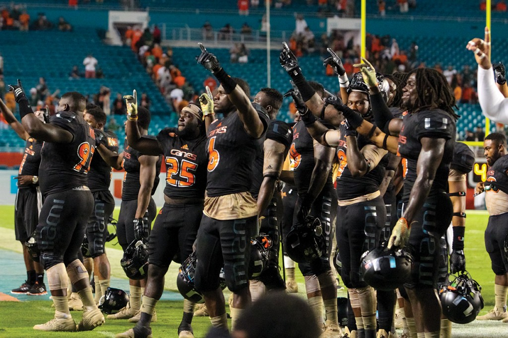 The football team sings the Alma Mater along with the crowd in light of the Hurricanes' 27-21 victory against the Caveliers Saturday evening at Sun Life Stadium. Hallee Meltzer // Photo Editor