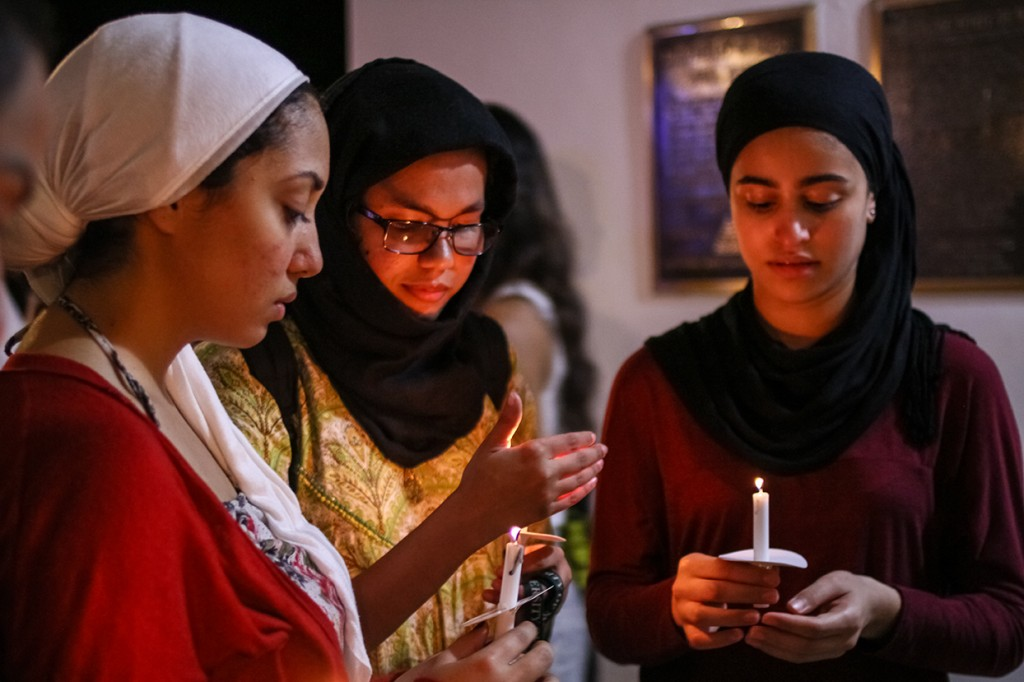 Sophomore Rowanne Ali, junior Areeba Imam, and sophomore Aya Eltantawy, vice president, president and treasurer of the Muslim Students' Association (MSUM), gather together during the candlelight vigil Wednesday evening at the UC Breezeway. The vigil was organized by the Council of International Students and Organizations (COISO) to encourage support and remembrance of those impacted by the recent acts of terror around the world. Erum Kidwai // Staff Photographer