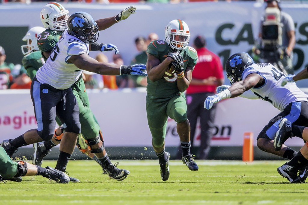 Former running back Duke Johnson (8) runs past two North Carolina defenders during last year's win against the Tar Heels. File Photo // The Miami Hurricane