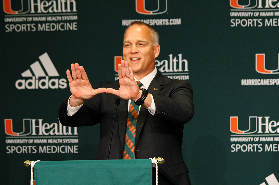 "After the press conference announcing his hire, Mark Richt, University of Miami's newest head football coach, throws up the ""U"" Friday morning in the Shalala Student Center. Erum Kidwai // Staff Photographer"