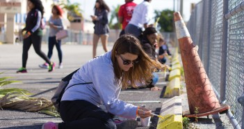 Freshman Tamara Popovska paints a parking spot alongside other students volunteering for the Martin Luther King Jr. Day of Service in Liberty City on Monday. The MLK Day of Service experienced a record turnout with nearly 150 student volunteers. UM partnered with the Miami Children's Initiative to bring volunteers to elementary and middle schools in Liberty City, where the volunteers worked on beautifying the area. Some of the projects included painting, laying mulch and cleaning up. The volunteers also got to spend time playing sports with children from local neighborhoods. Kawan Amelung // Staff Photographer