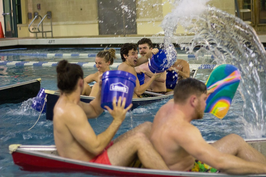Freshman Nick Hartman throws water at an opposing team during Friday's Battleship tournament at the Wellness Center pool. Teams aimed to sink the canoes of opponents using these buckets of water. Kawan Amelung // Staff Photographer