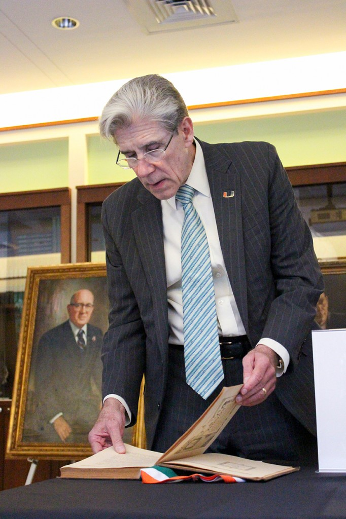President Frenk peruses the first published Ibis Yearbook, which is featured in an archives exhibit during the Firsts at UM event Wednesday evening in the Newman Alumni Center. Hallee Meltzer // Photo Editor