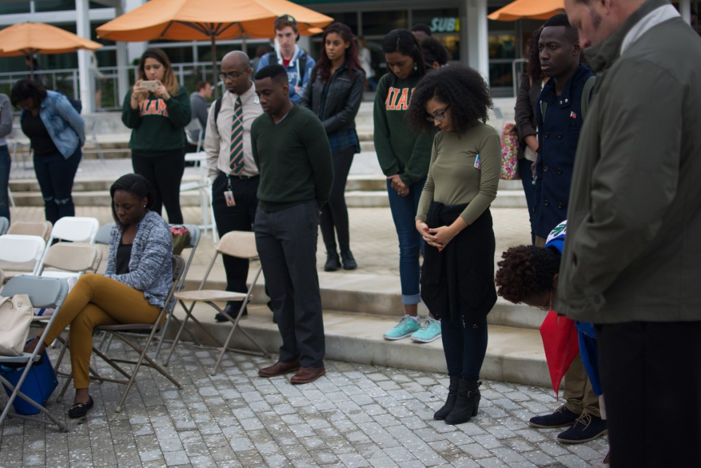 Students bow their heads in a moment of silence during Wednesday's Haiti earthquake remembrance ceremony at the Lakeside Patio. Planet Kreyol hosted the event to honor the victims of the earthquake that struck Haiti in 2010. Alisha Kabir // Staff Photographer