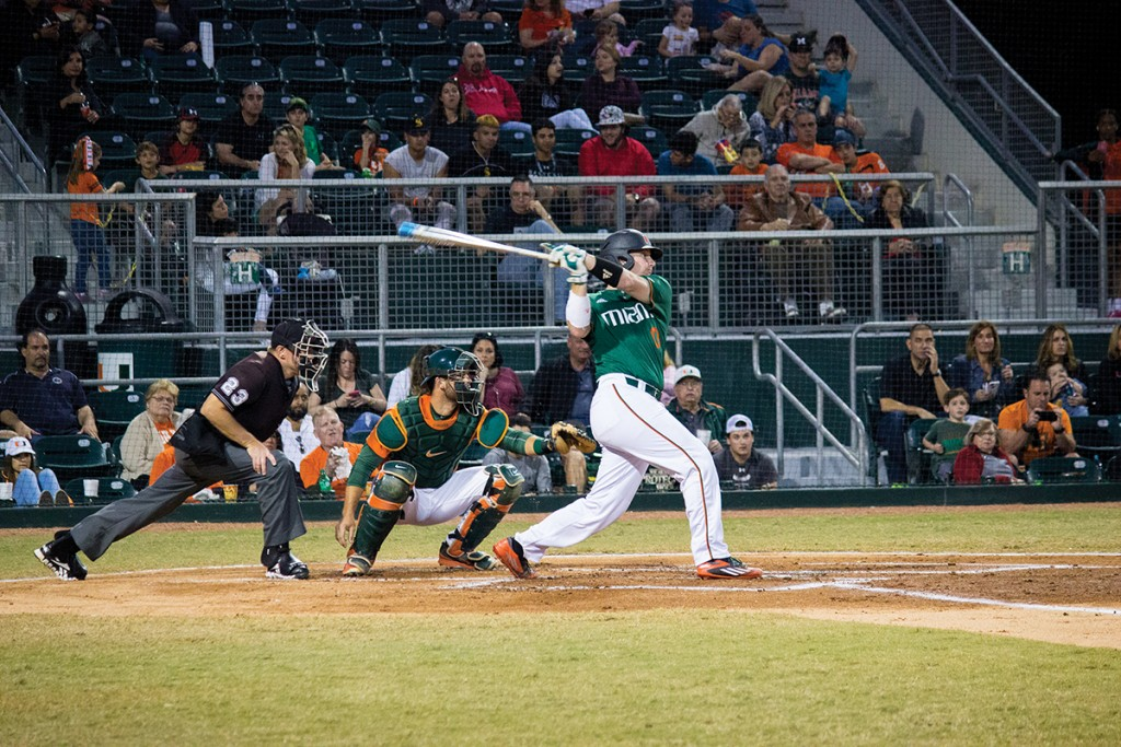 Junior catcher Zack Collins (0) hits during his at-bat during the Alumni game hosted at Mark Light Field at Alex Rodriguez Park Saturday night. Giancarlo Falconi // Staff Photographer