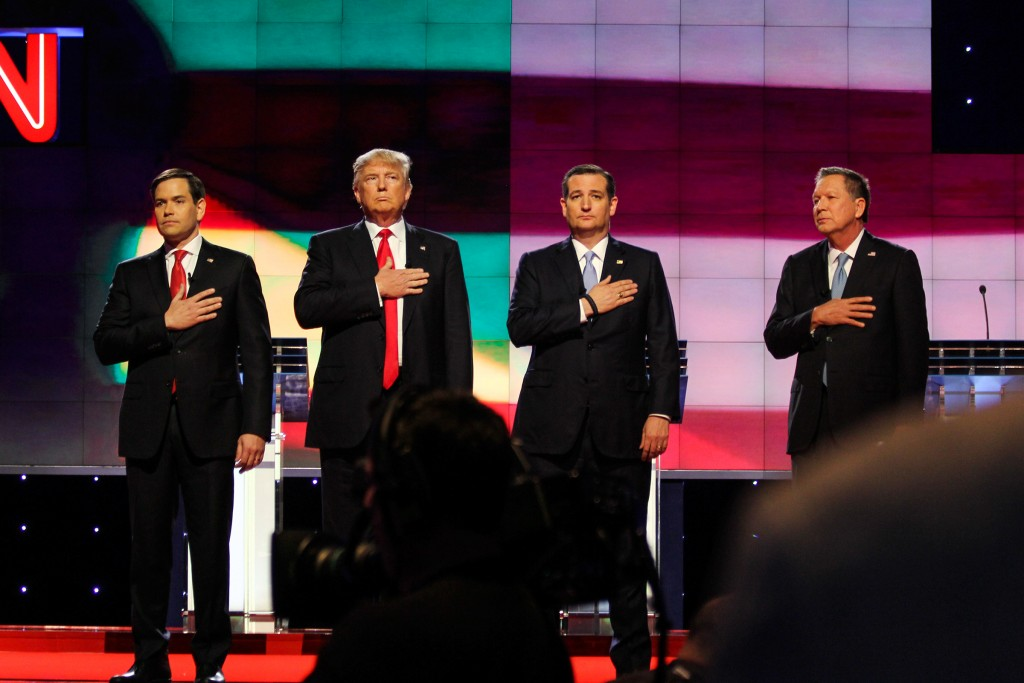 The four Republican candidates, Marco Rubio, Donald Trump, Ted Cruz and John Kasich hold their hands to their hearts during the National Anthem before the start of the GOP Debate Thursday night at the BankUnited Center. Victoria McKaba // Assistant Photo Editor