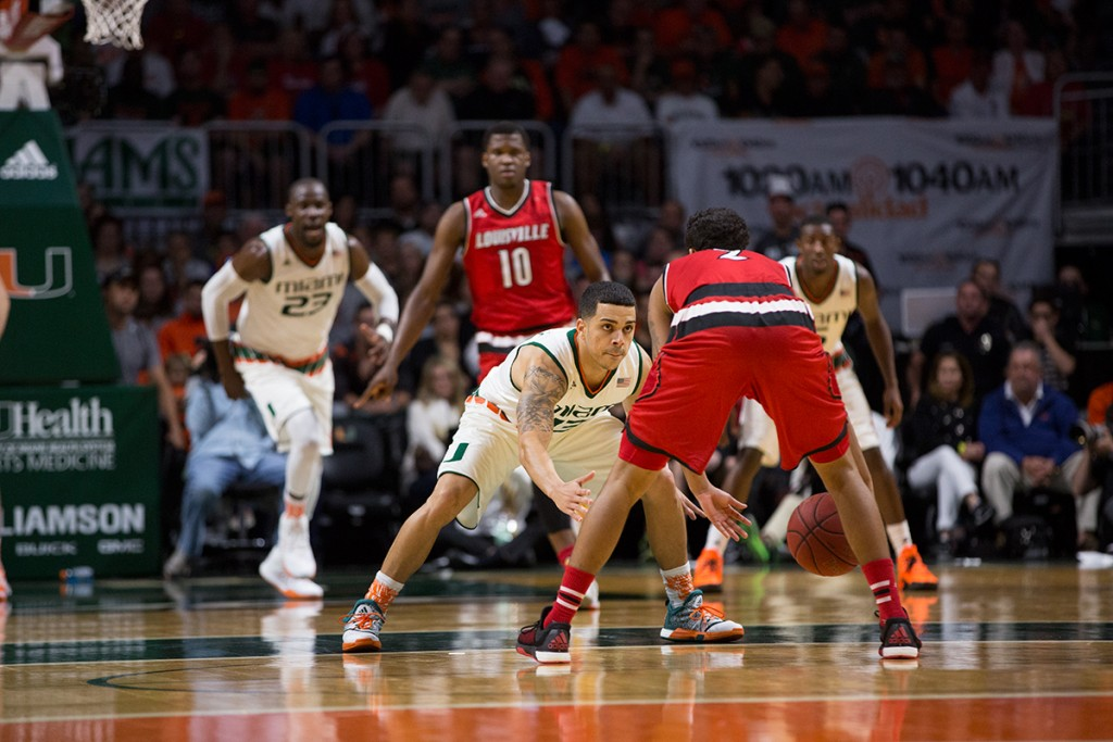 Redshirt senior guard Angel Rodriguez (13) defends the Louisville point guard at the BankUnited Center in a 73-65 win for the Canes. Nick Gangemi // Editor-in-Chief