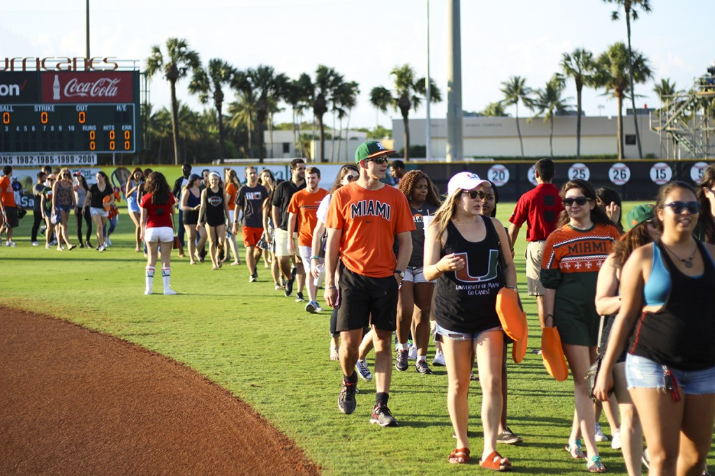 Seniors walk along the baseball field at Alex Rodriguez Park at Mark Light during the Senior Walk hosted by Category 5 Friday night. Kawan Amelung // Staff Photographer
