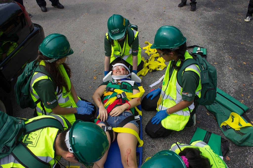 Members of CERT attend to a participant on a stretcher after removing her from a simulated car crash Sunday morning during the CERT Disaster Readiness Exercise. Giancarlo Falconi // Staff Photographer