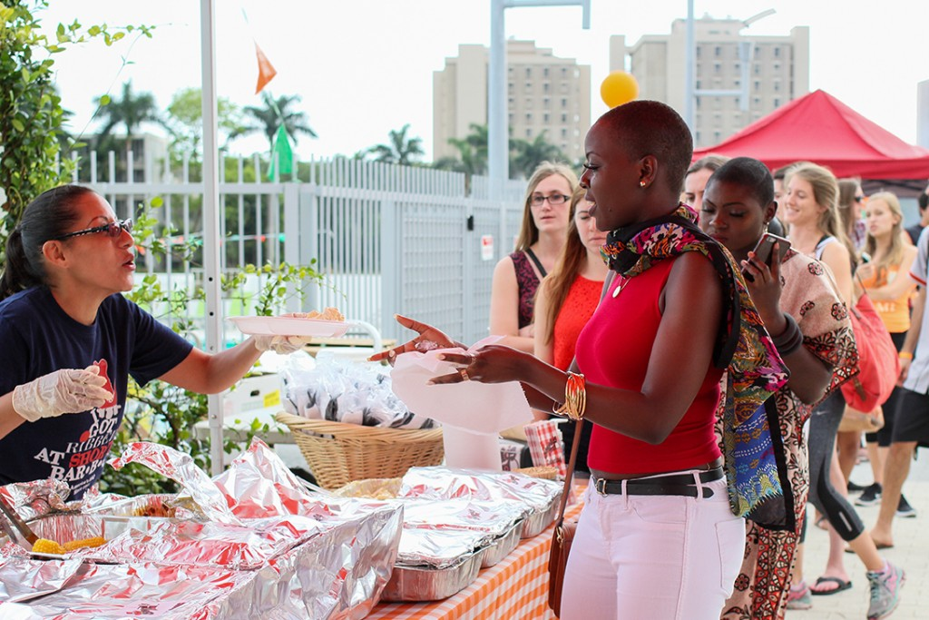 Senior Irene Mutiganzi receives food from Shorty's BBQ at the Senior Picnic Sunday evening on the Lakeside Patio. Erum Kidwai // Staff Photographer