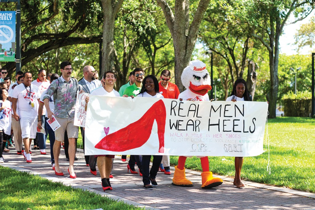Students strut through campus in red heels as part of Walk A Mile in Her Shoes hosted by Counseling Outreach Peer Education and Sexual Assault Resource Team Thursday afternoon. The walk raised awareness for domestic abuse and sexual assault. Kawan Amelung // Staff Photographer