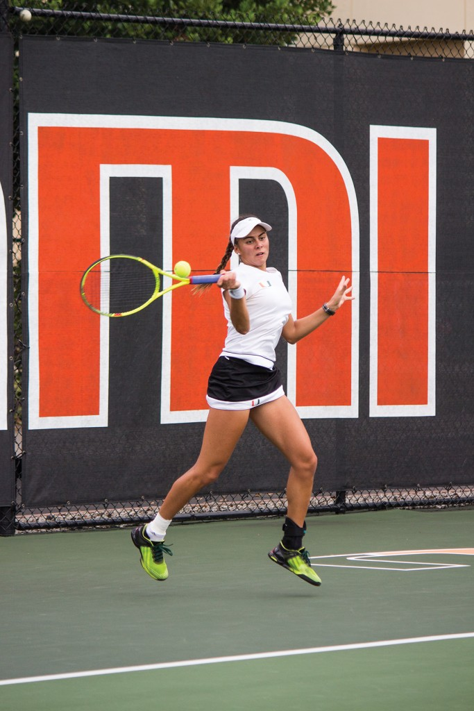 Freshman Ana Madcur hits a forehand shot during the women's tennis 6-1 win over Syracuse Friday afternoon at the Neil Schiff Tennis Center. Madcur had a 6-2, 6-1 win over Louisville's Olivia Boesing to finish her regular season 14-3 in singles. The Hurricanes' shutout the Cardinals 7-0. Shreya Chidarala // Staff Photographer