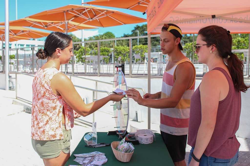 "Senior Student Government Senator Robert Renfro gives junior Olivia Gassner a raffle ticket at the ""Get To Know Your Senators"" event, hosted as part of Student Government Awareness Week, Wednesday afternoon on the Lakeside Patio. Hallee Meltzer // Photo Editor"