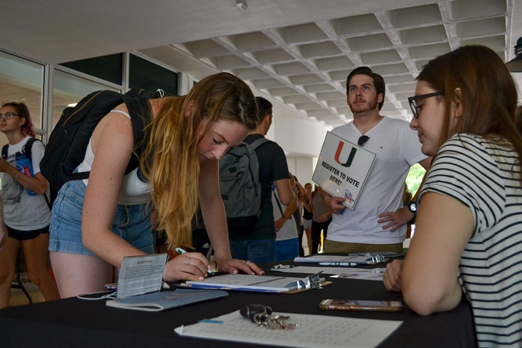 Sophomore Ralph Paz and junior Tess Schuit encourage students to register to vote during Get Out the Vote's tabling Wednesday afternoon in the UC Breezeway. Amanda Prats // Contributing Photographer