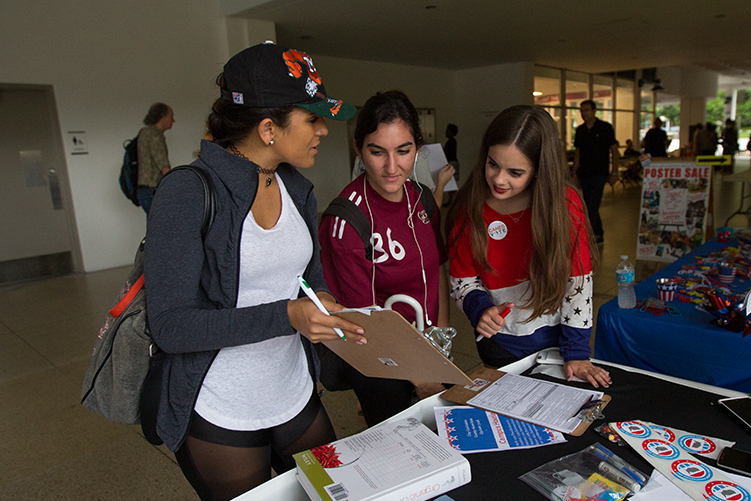 Senior and Get Out the Vote President Monica Bustinza helps junior Chelsea Chico and freshman Linda Shahin fill out forms during Get Out The Vote's registration drive Tuesday in the Breezeway. Nick Gangemi // Contributing Photographer