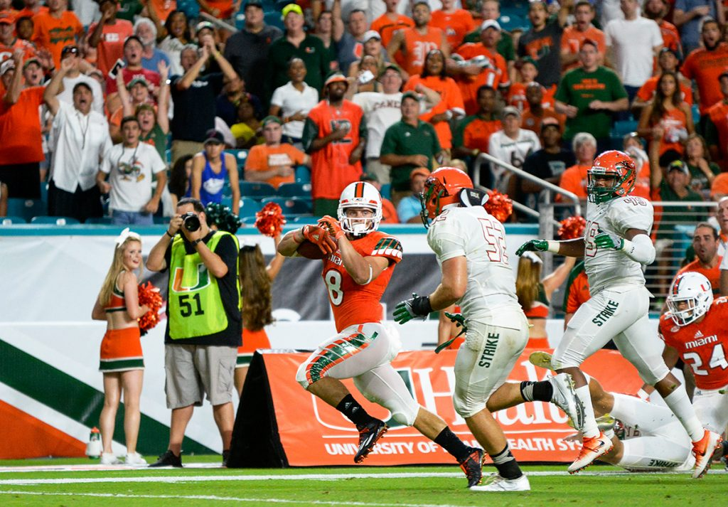 Junior wide receiver Braxton Berrios (8) runs past FAMU defenders for a touchdown during the Hurricanes' 70-3 win at Hard Rock Stadium. The Canes are anticipating their game against FAU this Saturday. Joshua White // Contributing Photographer
