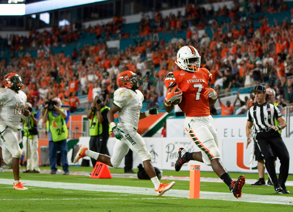 Redshirt junior running back Gus Edwards (7) glides into the end zone for a Hurricanes' touchdown during the 70-3 win over FAMU Saturday night at Hard Rock Stadium. Joshua White // Contributing Photographer