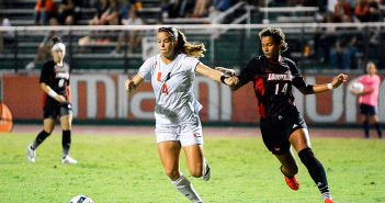 Junior forward Ronnie Johnson works her way around a Louisville player during the Canes' 3-0 win Thursday night at Cobb Stadium. Josh White // Staff Photographer