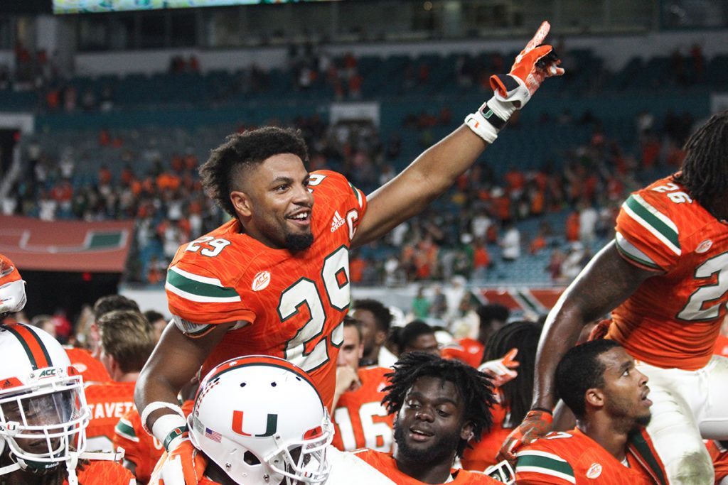 Senior defensive back Corn Elder (29) sits on the shoulder of his teammate and sings the alma mater as the team celebrates their seniors Saturday night after the Canes' win at Hard Rock Stadium. Victoria McKaba // Photo Editor