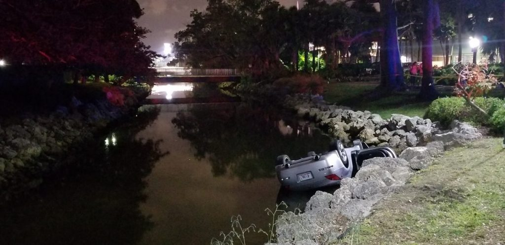 Car flips into campus canal