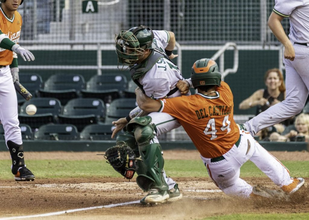 Adrian Del Castillo (44) collides with the pitcher on his way to home plate. Del Castillo went 3 for 4 and scored two runs for Miami.