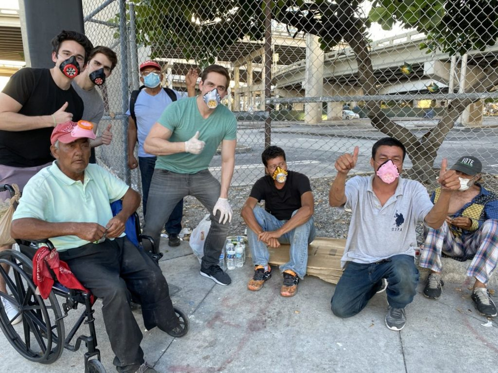 The Levine brothers pose alongside others wearing their masks during distribution on Sunday, May 4.