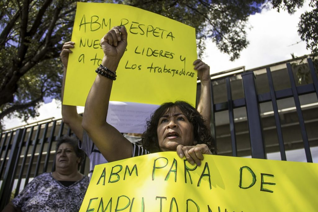 """Workers gathered along a fence facing US1 to protest being """"pushed to the limit"""" by ABM on Nov. 1."""