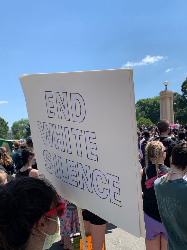 "A protestor holds a sign reading ""End White Silence"" during a demonstration outside of the Arkansas State Capitol in Little Rock, AR on Sunday, June 7, 2020."