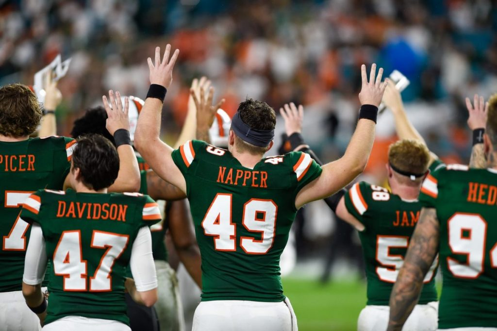 Then-freshman Long Snapper Mason Napper and other members of the canes football team hold up fours before the start of the fourth quarter on Nov. 9, 2019.